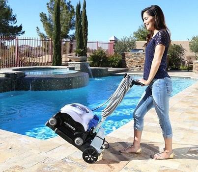 femme soulevant un chario avec un robot de piscine a cote d'une piscine