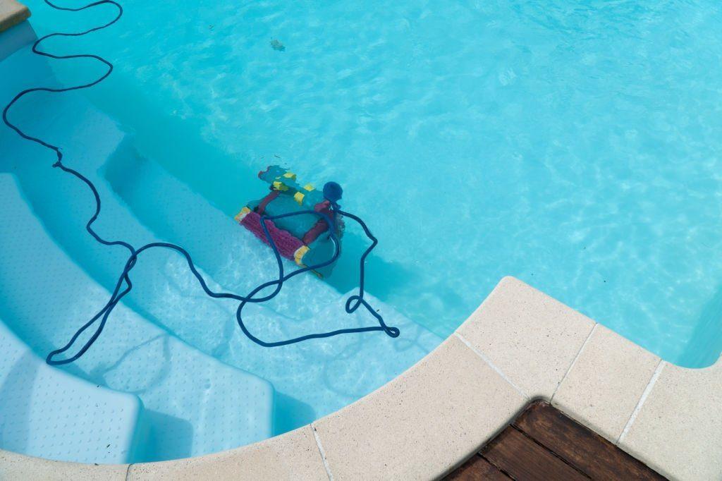 robot de piscine sous l'eau grimpant une marche d'escalier