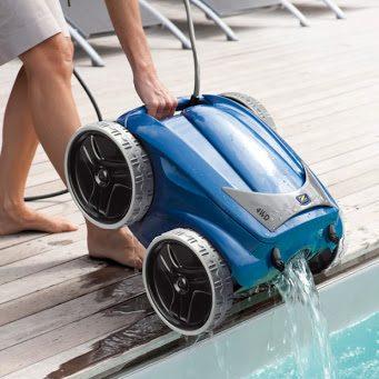 robot de piscine électrique soulevé par une femme, de l'eau sort de la machine qui se déverse dans la piscine