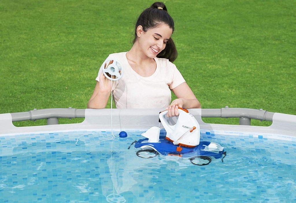 fille qui tient un robot de piscine sans fil dans une piscine hors sol